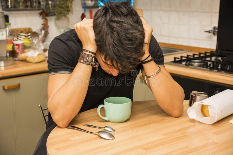 Hombre cansado con el café que se sienta en la tabla de cocina foto de archivo libre de regalías