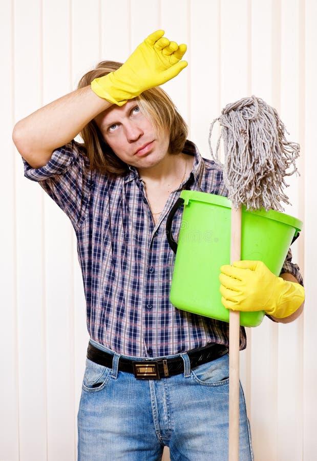 Hombre cansado con las fuentes de limpieza foto de archivo libre de regalías