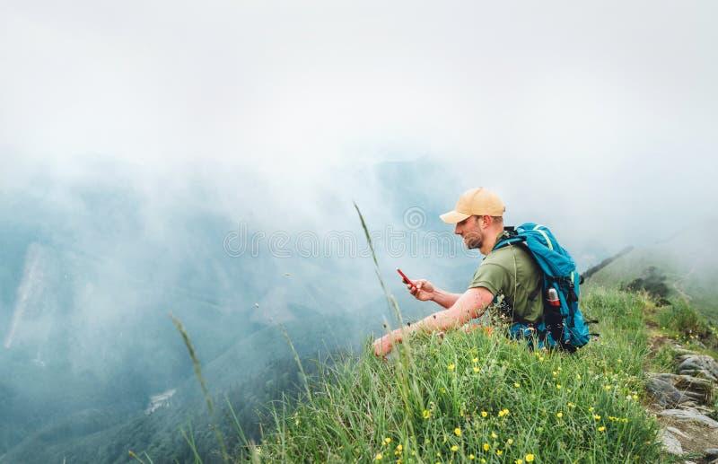 Hombre cansado del caminante con Internet de la ojeada de la mochila usando smartphone que disfruta de la parte inferior nublada  imagenes de archivo