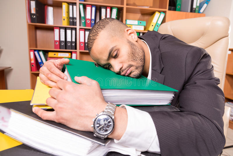 Hombre cansado del trastorno en oficina fotografía de archivo