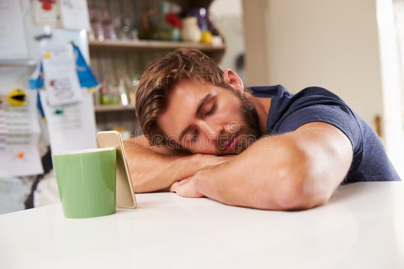 Hombre cansado dormido en la tabla de cocina al lado del teléfono móvil fotografía de archivo libre de regalías