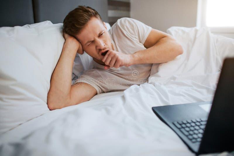 Hombre cansado joven que miente en cama esta mañana Él bosteza El individuo es soñoliento Mirada del hombre joven en el ordenador fotografía de archivo libre de regalías