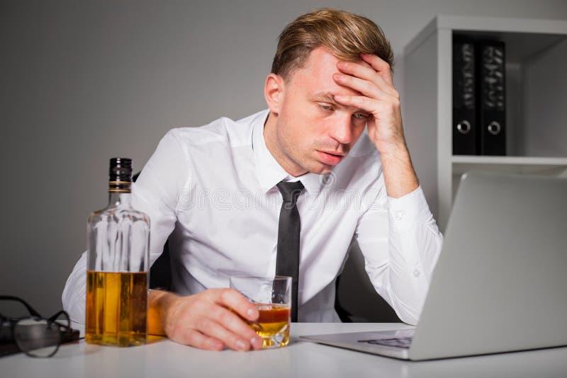 Hombre cansado que bebe en la oficina fotografía de archivo