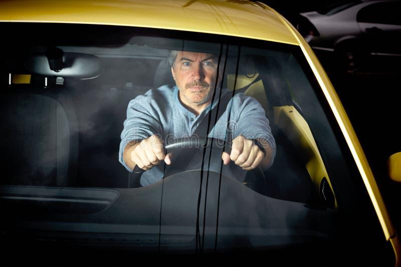 Hombre cansado que conduce el coche en la noche fotos de archivo