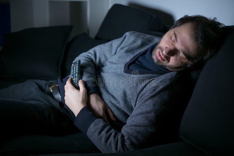 Hombre cansado que duerme delante de la pantalla de la TV foto de archivo