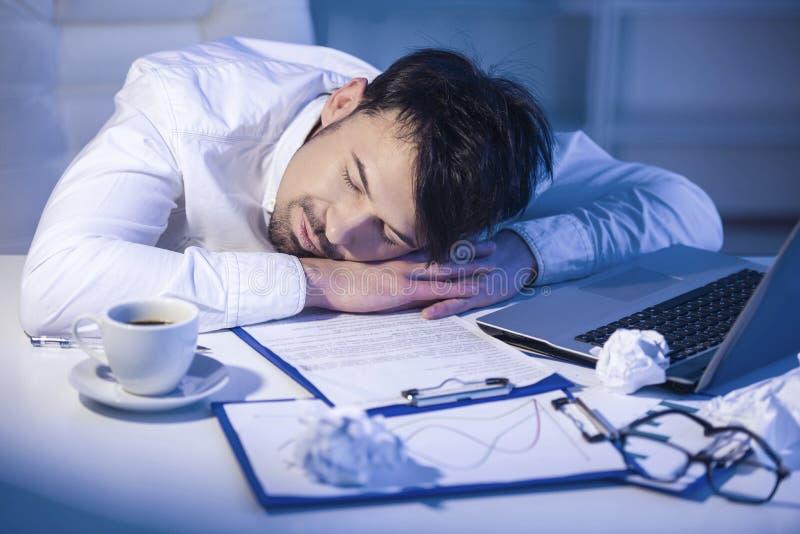 Hombre cansado que duerme en el trabajo con el ordenador imagen de archivo libre de regalías