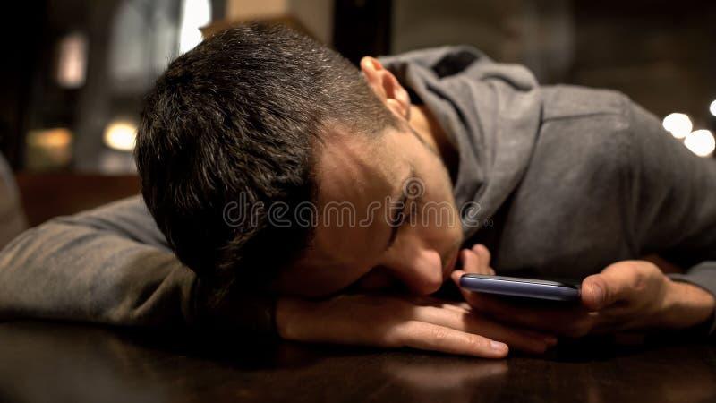 Hombre cansado que duerme en la tabla en el restaurante, smartphone de la tenencia, forma de vida ocupada imagen de archivo
