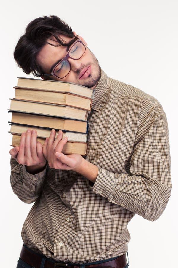 Hombre cansado que lleva a cabo los libros y dormir fotografía de archivo
