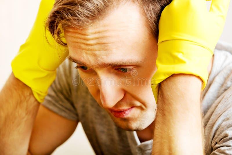 Hombre cansado que se sienta detrás del escritorio con el paño y los guantes fotos de archivo libres de regalías