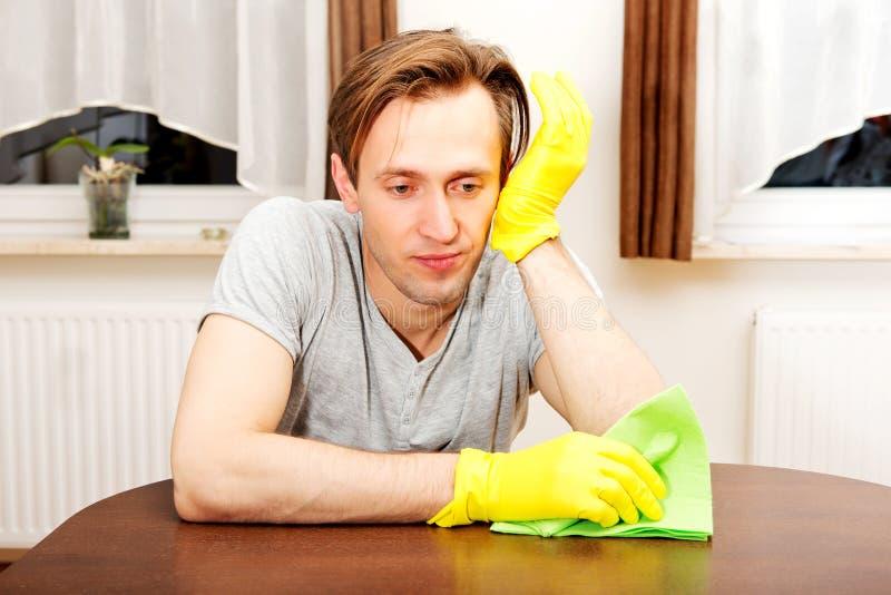 Hombre cansado que se sienta detrás del escritorio con el paño y los guantes foto de archivo