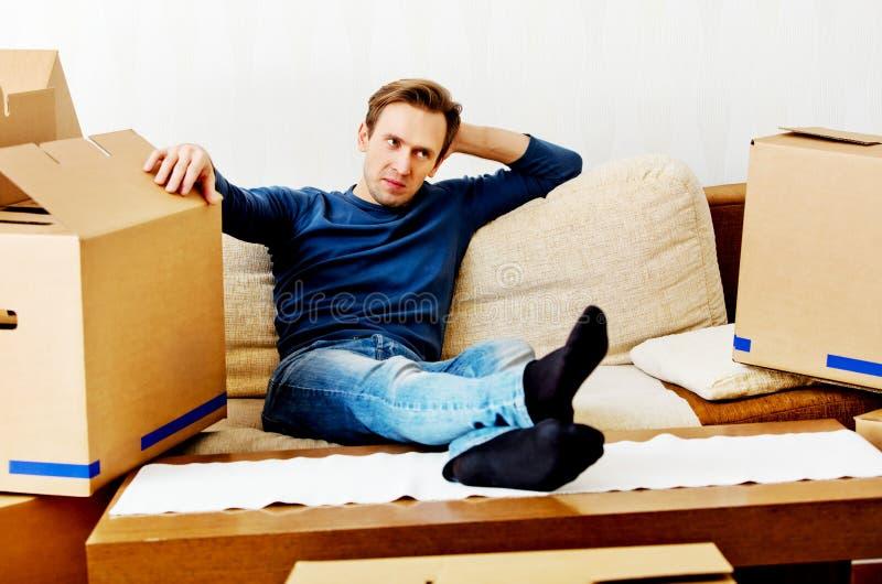 Hombre cansado que se sienta en el sofá con las cajas de cartón alrededor imágenes de archivo libres de regalías