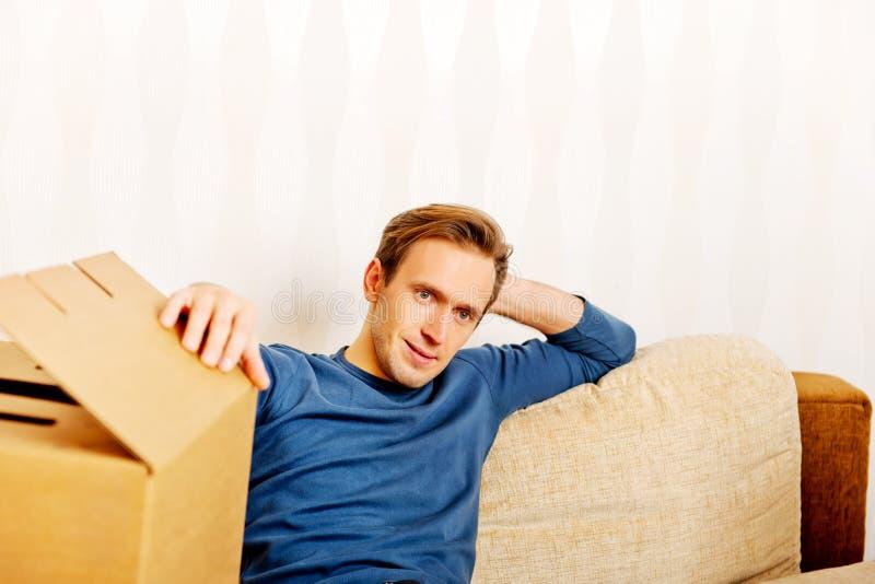 Hombre cansado que se sienta en el sofá con las cajas de cartón alrededor imagen de archivo