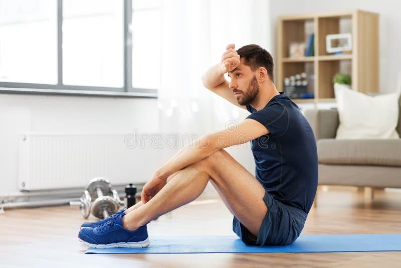 Hombre cansado que se sienta en la estera del ejercicio en casa fotografía de archivo libre de regalías