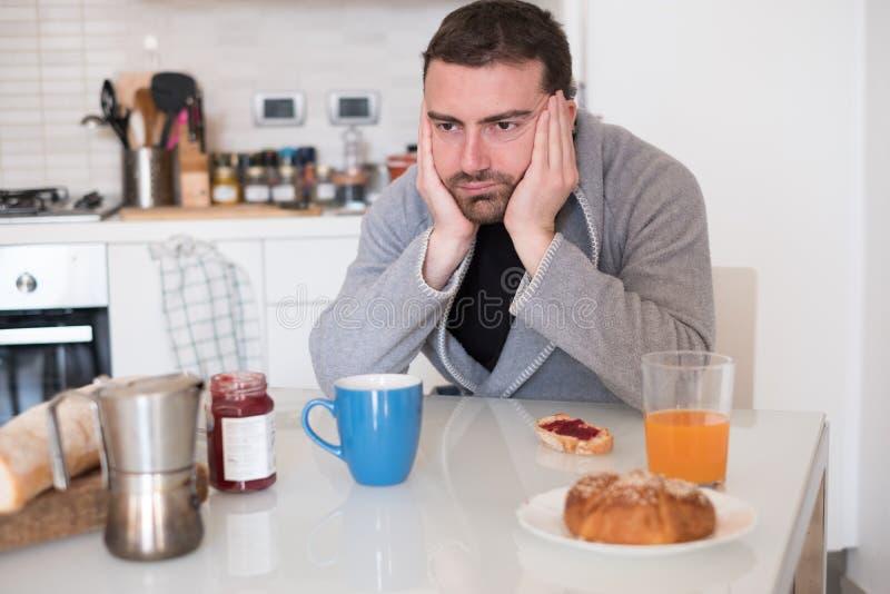Hombre cansado que se siente mal durante el desayuno de la madrugada foto de archivo libre de regalías