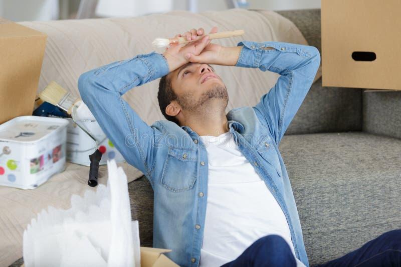 Hombre cansado que tiene rotura en sitio parcialmente pintado fotos de archivo