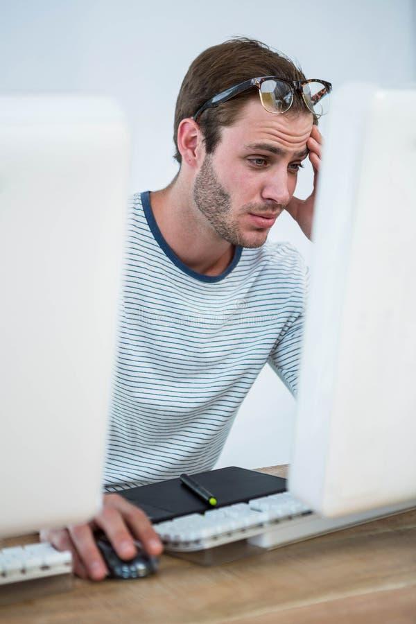 Hombre cansado que trabaja en el ordenador foto de archivo libre de regalías