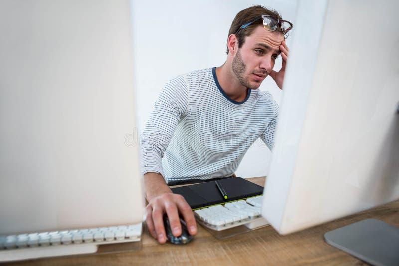 Hombre cansado que trabaja en el ordenador imágenes de archivo libres de regalías