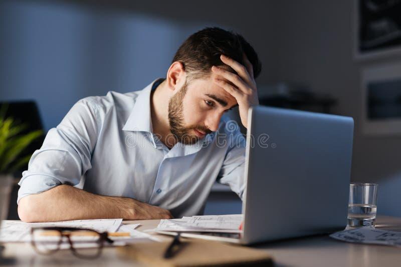 Hombre cansado que trabaja en horas extras en oficina de la noche foto de archivo