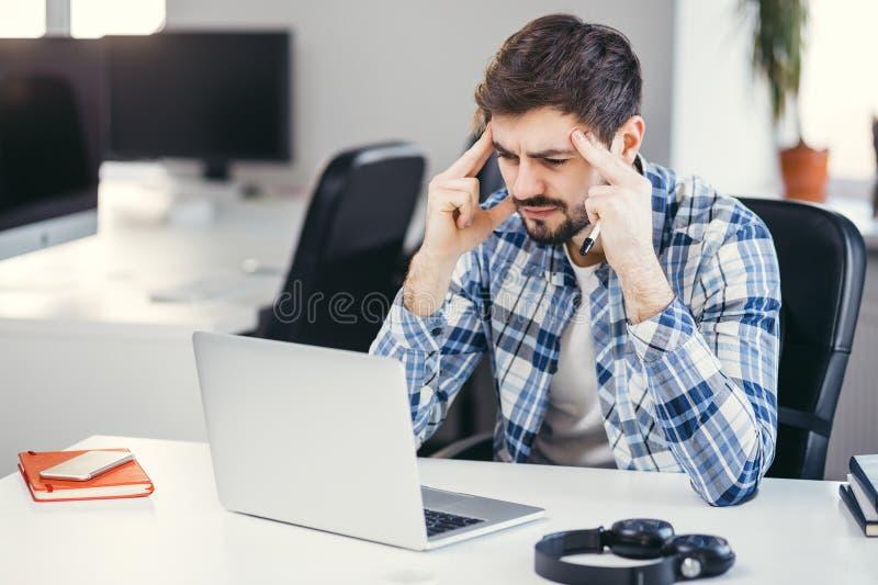 Hombre cansado que trabaja en la oficina del ordenador portátil fotografía de archivo libre de regalías