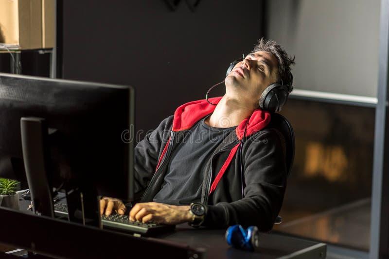 Hombre cansado que trabaja por el ordenador en el apartamento imagenes de archivo