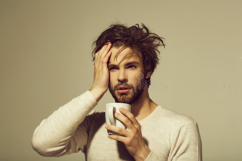 Hombre cansado soñoliento con la taza del control del dolor de cabeza de té foto de archivo