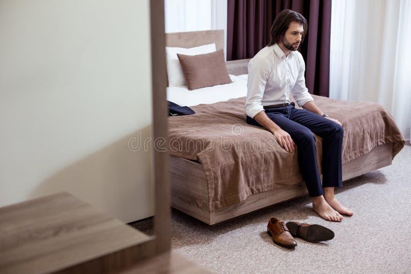 Hombre cansado triste que se sienta en la cama en el hotel foto de archivo libre de regalías