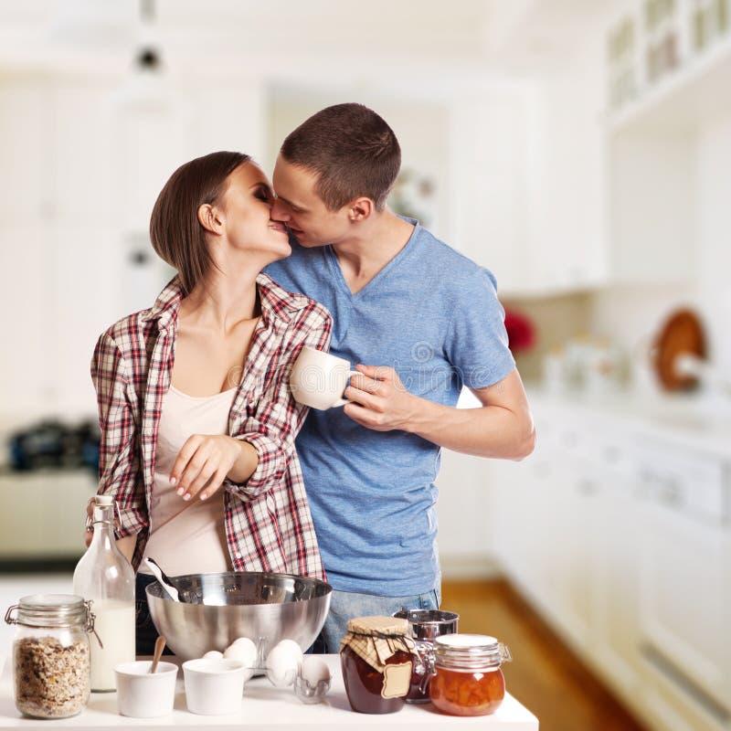 Hombre cariñoso que besa a su novia mientras que corta el pan para el desayuno en la cocina fotografía de archivo libre de regalías