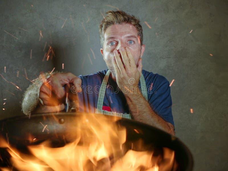 Hombre casero divertido y sucio joven del cocinero con el delantal en el choque que sostiene la cacerola en el fuego que quema la imagen de archivo libre de regalías