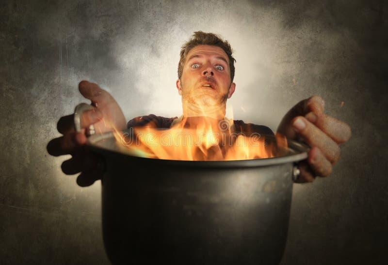 Hombre casero sucio atractivo y chocado joven del cocinero con el delantal que celebra cocinar el pote en el fuego que quema la c foto de archivo libre de regalías