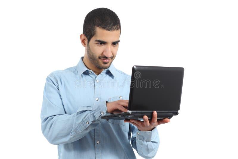 Hombre casual árabe que hojea un medio del social del ordenador portátil imagen de archivo libre de regalías