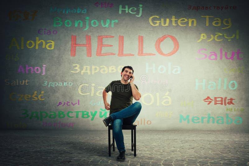 Hombre casual asentado en una silla que habla en el teléfono móvil Otros idiomas de discurso del encargado feliz con sus clientes imagen de archivo
