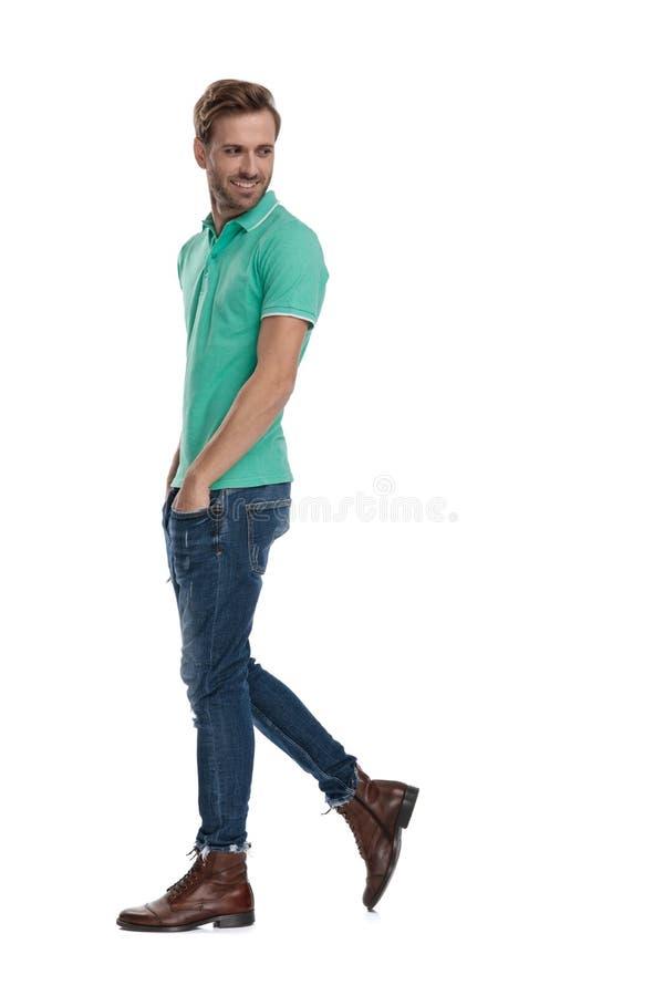 Hombre casual en polo verde que camina y que mira detrás fotos de archivo