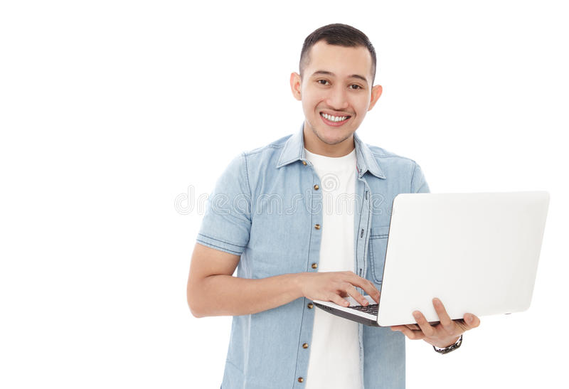 Hombre casual hermoso que se sostiene y que mecanografía en el ordenador portátil foto de archivo