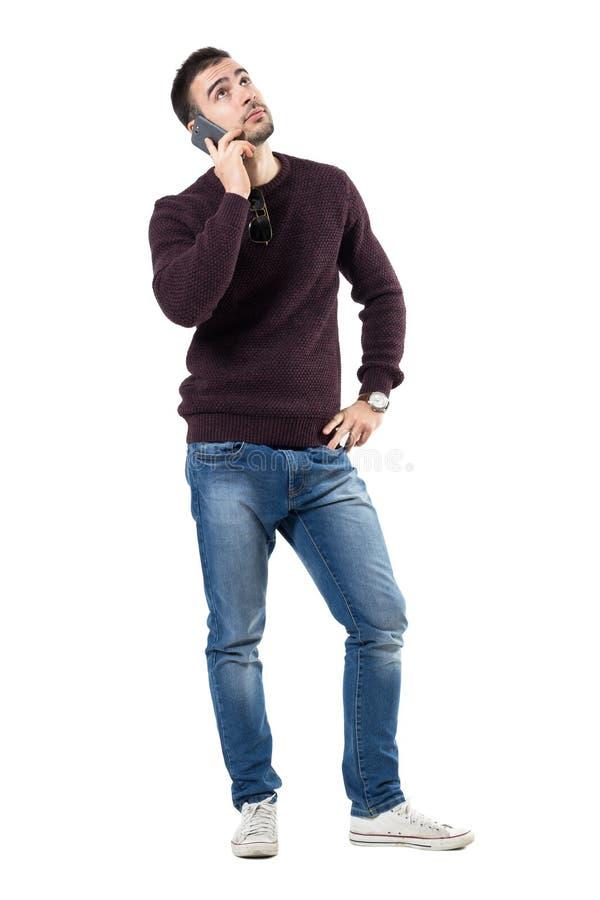 Hombre casual joven aburrido que escucha en el teléfono que mira para arriba imagen de archivo