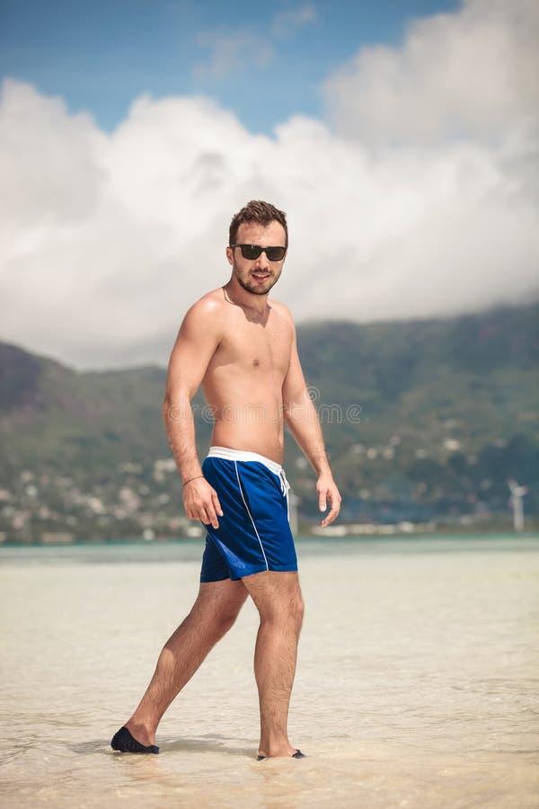 Hombre casual joven que camina en la playa foto de archivo