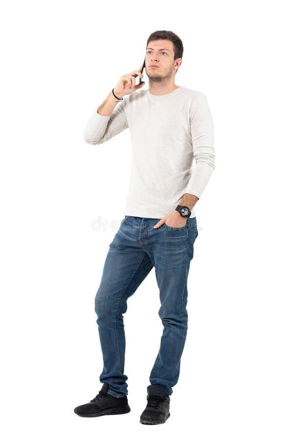 Hombre casual joven serio que habla en el teléfono móvil que mira para arriba foto de archivo