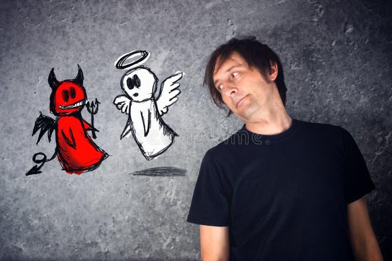 Hombre casual que mira el dibujo del garabato de la lucha del ángel y del diablo foto de archivo