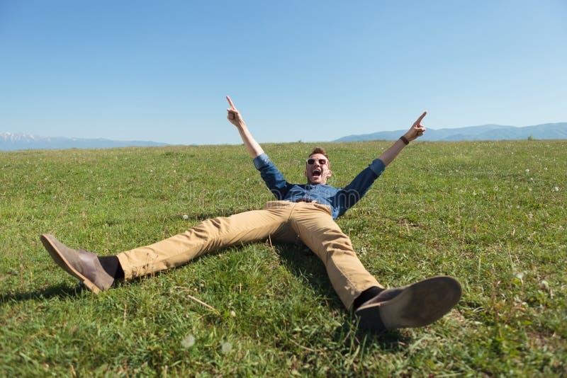 Hombre casual que pone en la hierba y animar fotos de archivo libres de regalías