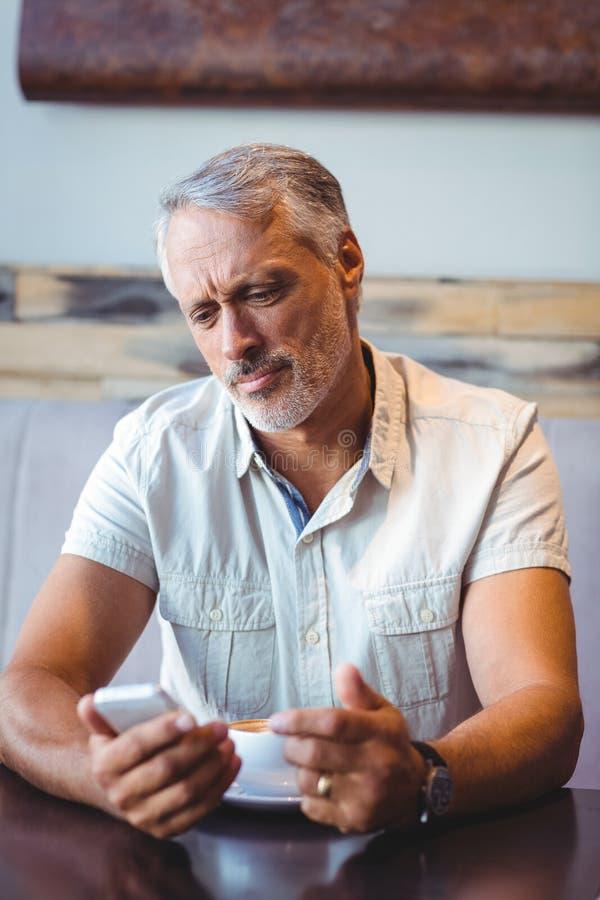 Hombre casual que usa el teléfono móvil en cafetería imágenes de archivo libres de regalías