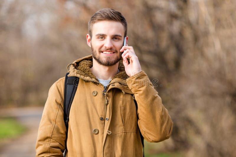 Hombre casual sonriente que habla en el teléfono al aire libre imagen de archivo