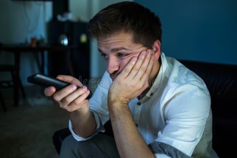 Hombre caucásico aburrido que ve la TV y zapping sentarse en un sofá en casa u hotel fotos de archivo libres de regalías
