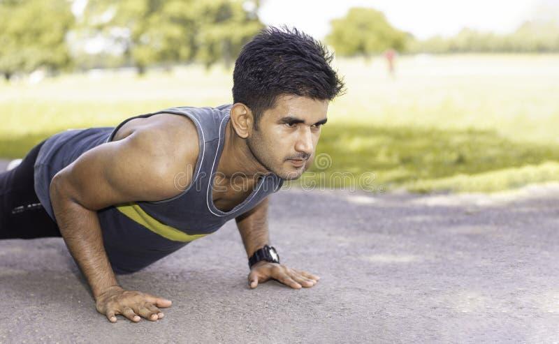 Hombre caucásico apto de los jóvenes con el cuerpo muscular que hace pectorales al aire libre en día de verano soleado foto de archivo libre de regalías