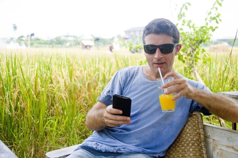 Hombre caucásico atractivo 30s que sonríe sentada feliz y relajada en la cafetería del campo del arroz en viaje del día de fiesta fotografía de archivo