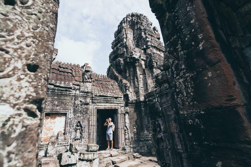 Hombre caucásico con cámara en medio de las ruinas del complejo del templo Angkor Wat en Siem Reap, Camboya. fotos de archivo