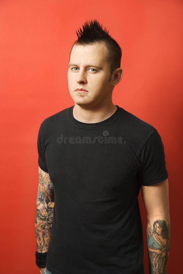 Hombre caucásico con los tatuajes y mohawk. foto de archivo