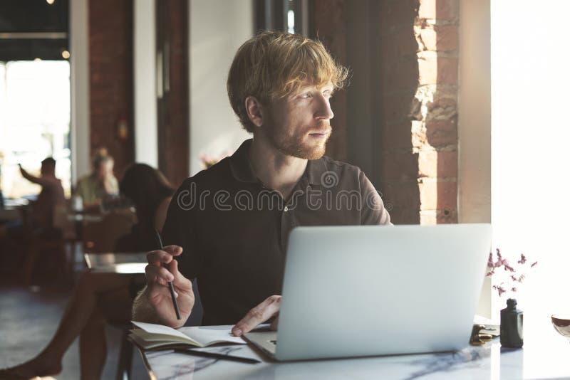 Hombre caucásico del jengibre alegre que usa el ordenador y smartphone que se sienta en el café que come café imágenes de archivo libres de regalías