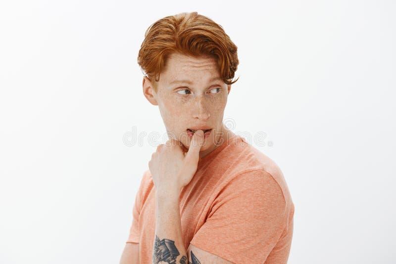 Hombre caucásico del pelirrojo que vacila, tomando la decisión en mente, siendo dudoso sobre propia opción, dando vuelta al revés foto de archivo