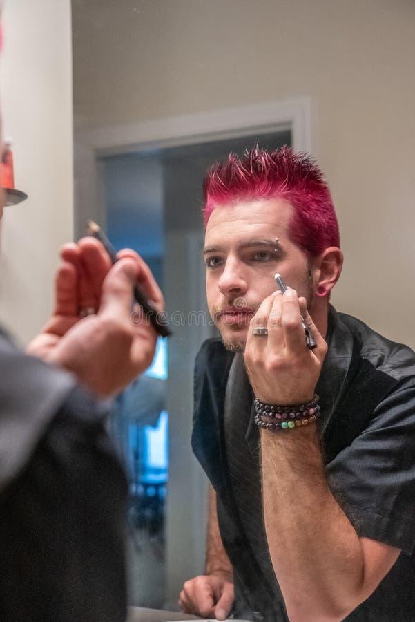Hombre caucásico diverso con el pelo rosado claveteado que aplica lápiz de ojos en el espejo imagen de archivo libre de regalías