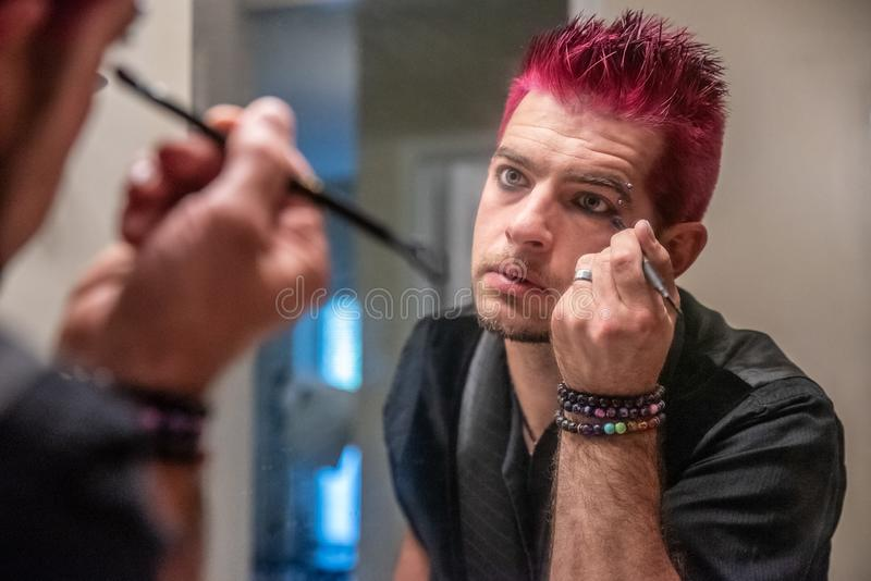 Hombre caucásico diverso con el pelo rosado claveteado que aplica lápiz de ojos en el espejo fotografía de archivo