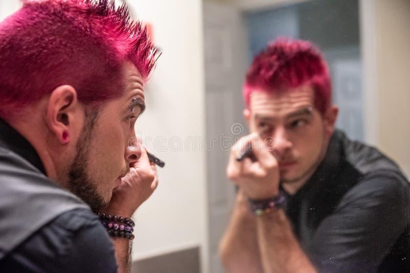 Hombre caucásico diverso con el pelo rosado claveteado que aplica lápiz de ojos en el espejo foto de archivo libre de regalías